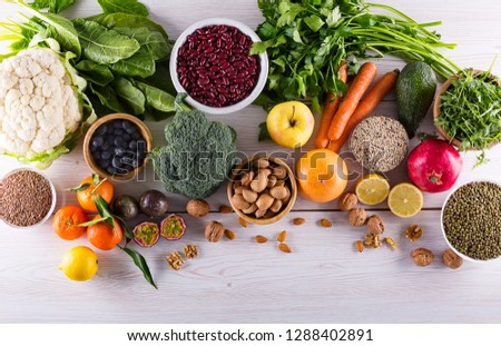 Healthy food clean eating: fruit, vegetable, seeds, superfood, cereals, leaf vegetable on black wood background with copy space, top view. #1288402891