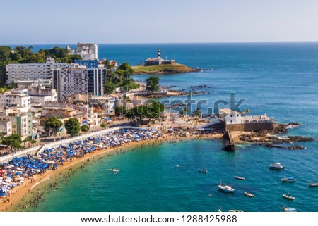 Aerial view of Salvador da Bahia, Brazil, showing Porto da Barra Beach and historical landmarks Barra Lighthouse and Santa Maria Fort during summer.