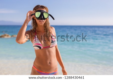 Beautiful young woman standing on the beach with diving goggles looking into the camera #1288430461