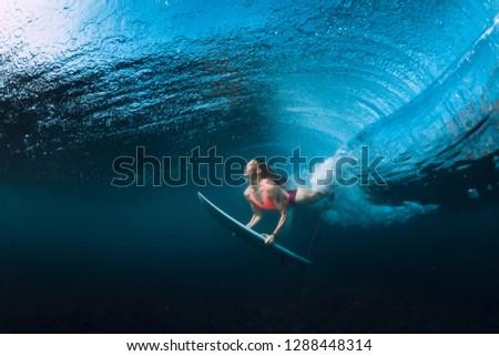 Surfer woman dive underwater with under barrel wave. #1288448314