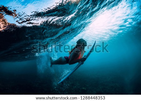 Attractive surfer woman dive underwater with under wave and sun light.
