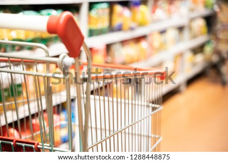 Shopping trolley cart with shallow DOF against modern supermarket aisle blurred background #1288448875