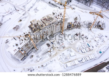 aerial top view of city construction site. tower cranes for building of new apartments under snow in winter #1288476889