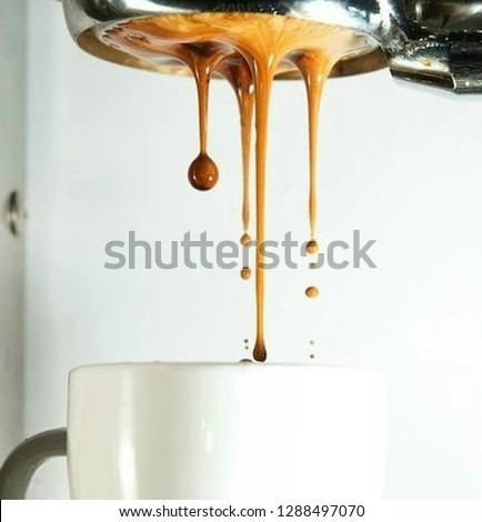 Espresso pouring from coffee machine into coffee cups #1288497070