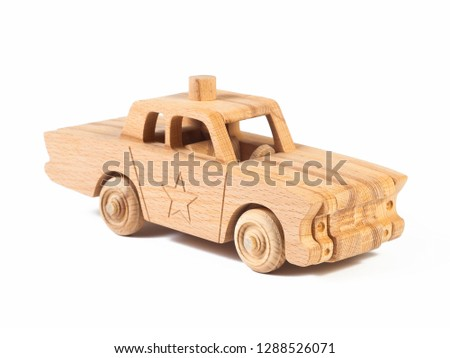 Photo of a wooden  police car  of beech. Toy made of wood retro car on a white isolated background