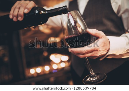 Close up. Elegant waiter pours red wine from bottle into glass at restaurant. Sommelier tasting wine in restaurant. #1288539784