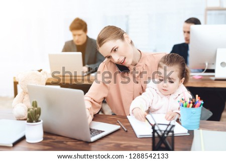 The woman with the child came to work. She works with her daughter in her arms. This is a business office. #1288542133