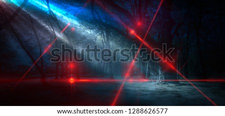 Silhouette of a man in a dark, gloomy forest. Laser beams of red color . #1288626577