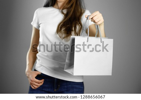 Girl holding a gray paper gift bag. Close up. Isolated background. #1288656067