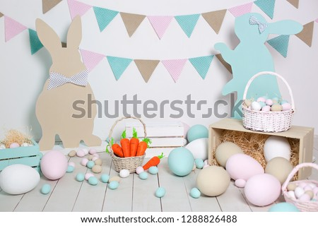 Easter! A lot of colorful Easter eggs! Easter decoration of a room with rabbits and baskets with eggs. Farm. harvesting. Basket with carrots and easter bunnies. Easter decor. Holiday flags on wall #1288826488