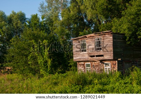 Light blue sky in the warm summer over the old abondoned house built from wood far away in the forest. Green trees near. Travelling on the suburb roads  #1289021449