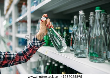 Young woman buying mineral water in supermarket #1289025895