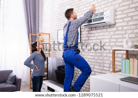 Young Woman Looking At Male Technician Repairing Air Conditioner Mounted On Brick Wall Royalty-Free Stock Photo #1289075521