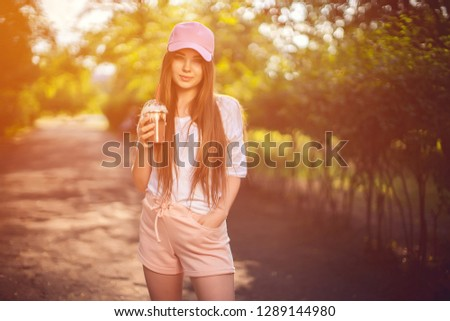 Pretty confident brunette in cap and summer outfit holding chocolate drink in cup looking at camera with smile in nature #1289144980