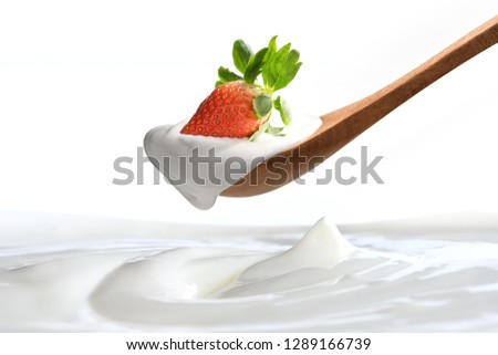 Plain yogurt on a spoon with fresh  strawberry on top hanging above of plain yogurt isolated on white background #1289166739