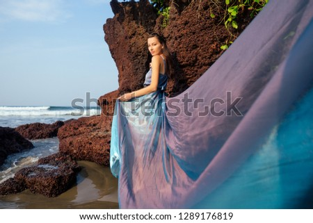 fashion pretty female model posing on a beach with rocks in a long butterfly chameleon dress waterfall of skirt plume train.sensual perfume with a beautiful and young brunette woman wave tropical sand #1289176819