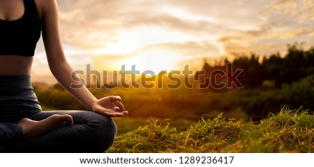 Young woman practicing yoga in the nature.female happiness. Landscape background