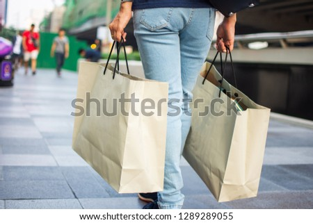 rear woman with paper shopping bag. soft focus. #1289289055