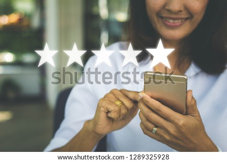 Businesswoman pressing five stars (5) rating on virtual touch screen at smartphone .Customer service evaluation concept. #1289325928