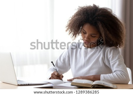 Focused African American teenage girl sit at table with laptop studying with handbooks, serious concentrated black teenager do homework at home, write down in notebook, using computer and textbook #1289386285