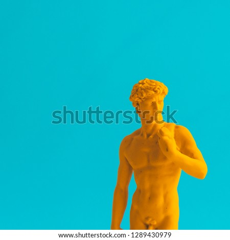 Creative concept of yellow neon David is a masterpiece of Renaissance sculpture created  by Michelangelo. Vaporwave style. Turquoise background #1289430979
