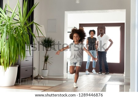 Excited little funny african girl running exploring big modern house moving in, happy black parents and kid daughter coming into new home, cute mixed race child having fun in hallway, family mortgage #1289446876