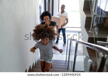 Happy cute black child running up stairs moving in two story modern house with parents carrying boxes, excited kid having fun going upstairs enjoying relocation into new home, african family mortgage #1289446924