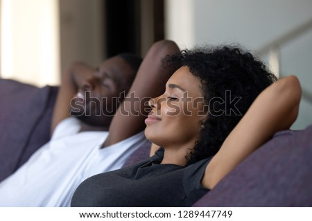 Relaxed african couple enjoying peaceful rest breathing fresh air at home on comfortable couch, happy lazy young black couple having nap leaning on sofa relaxing in living room feel no stress free #1289447749