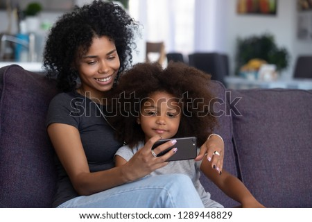 Happy smiling african american mother and little daughter taking selfie on smartphone, mixed race mom and child girl making video call on cellphone, mommy kid watch cartoons using phone app at home #1289448829