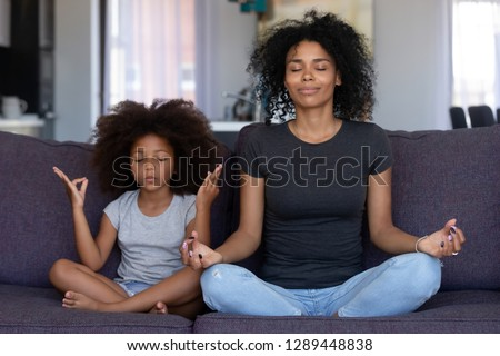Mindful african mom with cute funny kid daughter doing yoga exercise at home, calm black mother and mixed race little girl sitting in lotus pose on couch together, mum teaching child to meditate #1289448838