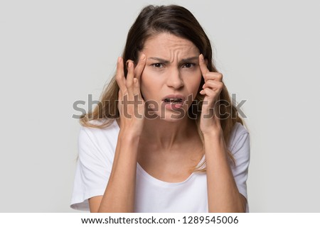 Stressed young woman confused about facial wrinkles aging skin on forehead or crows feet looking at camera isolated on studio background, upset worried girl having headache touching temples, portrait Royalty-Free Stock Photo #1289545006