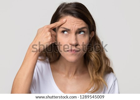 Dissatisfied stressed depressed young woman touch forehead worried about skin wrinkle isolated on studio background, cosmetology botox injection anti aging cream concept, cosmetology facial treatment #1289545009