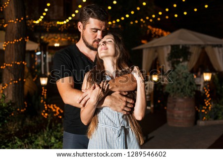 happy couple in love man and woman hugging. boy and girl on an evening date in a restaurant #1289546602
