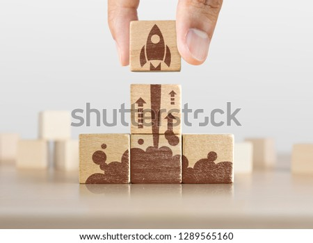 Business start up, start, new project or new idea concept. Wooden blocks with launching rocket graphic arranged in pyramid shape and a man is holding the top one. #1289565160