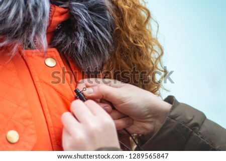 Sound engineer fastens lavalier microphone on actor's clothes