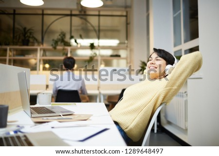 Young office manager with headphones enjoying her favorite music by workplace in front of laptop #1289648497