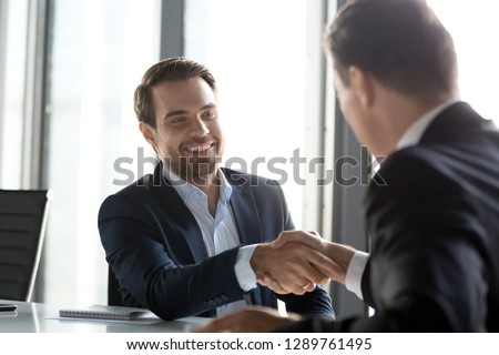 Happy businessmen in suits shaking hands after successful negotiations at meeting, male partners making business deal or good impression, thanking promising loyalty, respect gratitude handshake #1289761495