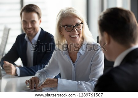 Friendly middle aged female leader laughing at group business meeting, happy old businesswoman enjoying fun conversation with partner, smiling mature business coach executive talking to colleague #1289761507