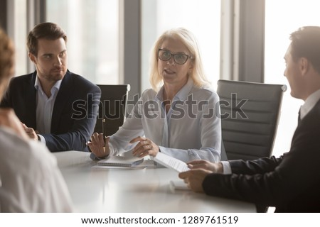 Serious middle aged businesswoman talks at group board executive meeting, confident mature old female leader speaking discussing work offers solution negotiating with partners at corporate briefing Royalty-Free Stock Photo #1289761519