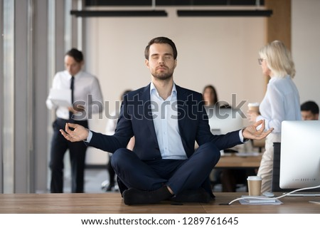 Mindful calm businessman in suit meditating at office sitting in lotus position on work desk, successful ceo executive doing yoga exercise at workplace, peace of mind, no stress free relief concept #1289761645