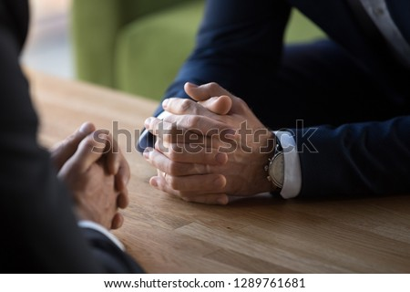 Clasped male hands of two businessmen negotiate at table, hr recruiter making hiring decision at difficult job interview, opponents dialogue debate, business confrontation challenge concept, close up #1289761681