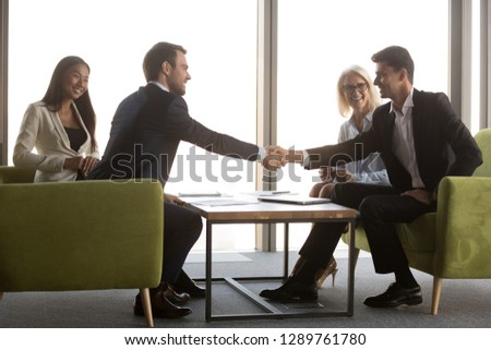 Arabic and caucasian male business partners handshaking at meeting greeting, making international partnership investment deal, diverse happy businessmen shaking hands as respect or gratitude concept #1289761780