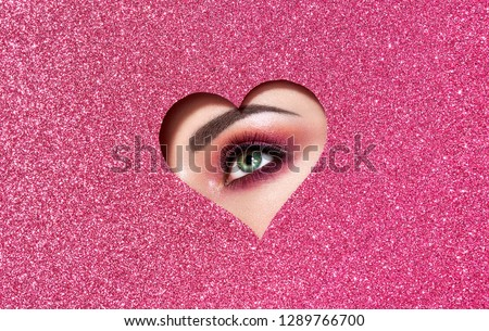 Conceptual photo of Valentine's day. Eye of Girl with Festive Pink Makeup. Paper heart on a pink background. Love symbols Valentines day #1289766700