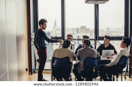 Group of multiethnic male arhitecture designers in casual wear gathered around the table in modern office, the young caucasian male speaker representing his ideas about trends of further development #1289802946