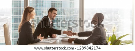 Horizontal photo diverse businesspeople gather at modern office boardroom, black boss congratulate partner make deal effective negotiations signing agreement concept, banner for website header design #1289842174