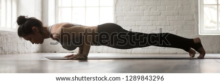 Horizontal full length side view photo young sporty woman wearing activewear doing yoga four limbed staff exercise chaturanga dandasana workout at home or sport center banner for website header design #1289843296