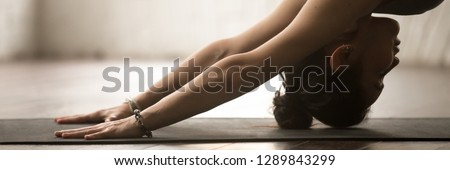 Horizontal photo banner woman practice yoga doing downward facing dog exercise stand adho mukha svanasana pose, physical and internal healthcare concept, website header design with copy space for text #1289843299