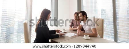 Horizontal photo modern office meet realtor young couple sitting at desk discuss new house plan first home, agent show build project on tablet banner for website header design with copy space for text