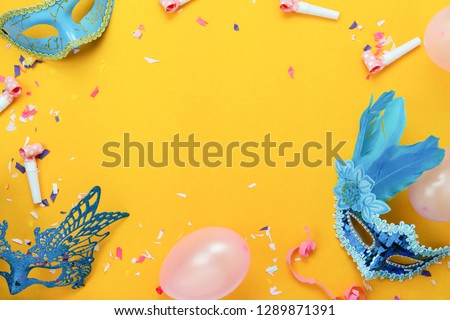 Table top view aerial image of beautiful colorful carnival festival background.Flat lay accessory object the mask & decor confetti and balloon on modern yellow paper at home office desk studio.