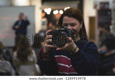 Rostov-on-Don, Russia, November 29, 2018, a girl photographer looks at the camera and smiles at the event during the work #1289914978